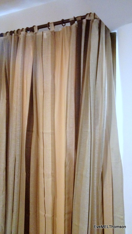 Striped beige and brown light-weight curtains hang over the old lined beige curtains.